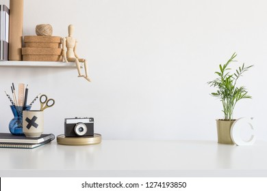 White desk with cork boxes, supplies, notebooks, ivy on a shelf and white wall for mock up or copy space.
