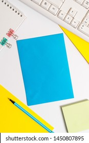 White desk with different sizes, color and types of paper. Notebook papers with binder clip near keyboard. Colored sheets with empty space and blue pen and office supplies.