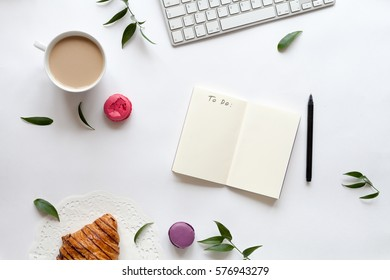 White desk with flowers, notebook, keyboard, macaroons and cup of coffee