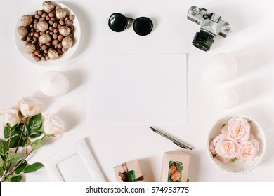 White desk with glasses, roses, candles, gifts, pen and film camera. Empty sheet in the middle. Top view, flat lay, copyspace.