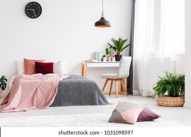 White desk and gray chair standing between a large window and king size bed in pastel bedroom interior for a girl