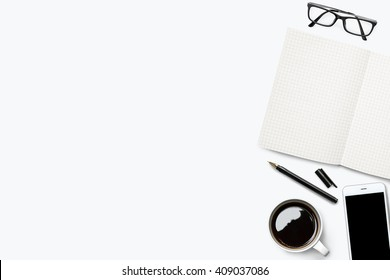 White desk with grid lined notebook and other supplies. Top view with copy space.
