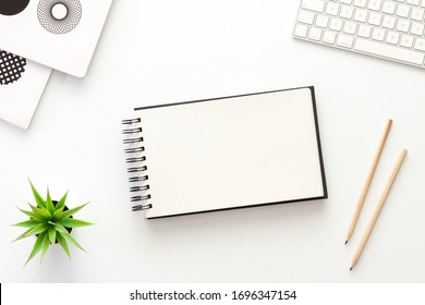 A white desk with an open sketchbook. Mockup.