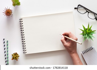 A white desk with an open sketchbook and a woman's hand. Drawing. View from above. Creative desk. Mockup.