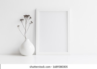 White desk with photo frame and  minimal round vase with a decorative twig against white wall.