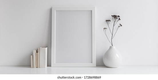Weißer Schreibtisch mit Fotorahmen, Bürobedarf, Schachteln und frisches natürliches Blatt in Designvase.