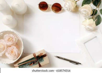 White desk with sunglasses, roses, candles, pen and vintage white tray. Empty sheet in the middle. Celebration card concept. Top view, flat lay, copyspace.
