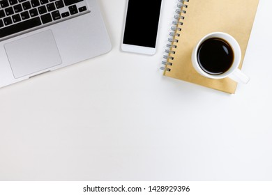White desk. There are computer, notebooks, white coffee cups.Top view and copy space