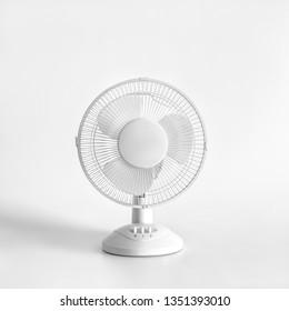 White desktop electric fan on light white background. Minimal concept.