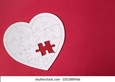 White details of a puzzle on blue background. A puzzle is a puzzle from small pieces. Heart shape of the details.