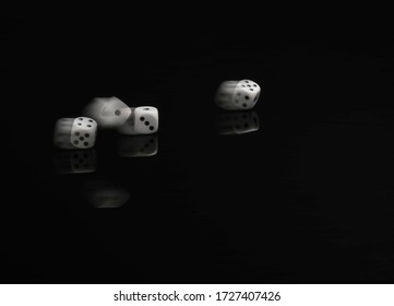 White dice captured with motion blur as they are thrown on a black table