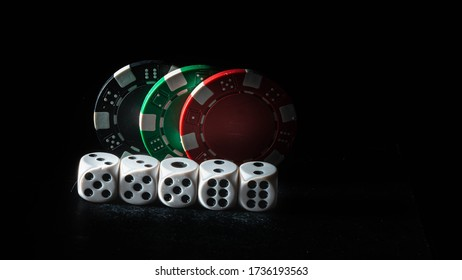 White dice and colorful chips isolated on black background. Multicolor tokens. Dice and casino chips