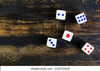 white dice lie on a black wooden table