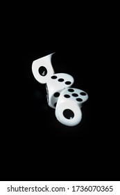 White dice in motion on a black background. Dice are isolated and in the air