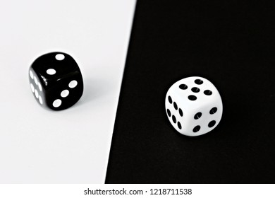A white dice on a black background and a black dice with a white background lie side by side - concept with contrasts and dice