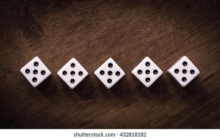 White dice on wooden background. All number five. Concept of luck, chance and leisure fun.
