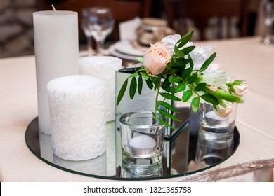 white different candles and a rose standing on a round mirrored tray on a table at a wedding banquet