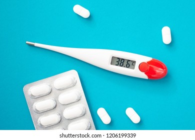 White digital clinical thermometer shows fever heat temperature and pills on blue background