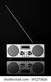 White digital DAB radio, stereo speakers on black background with extended aerial