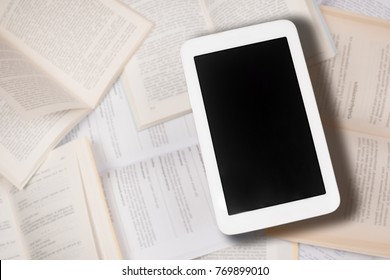 The white digital tablet is on blurry books background. Digitalisation concept.