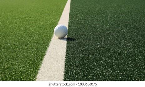 White dimple hockey ball on astro turf