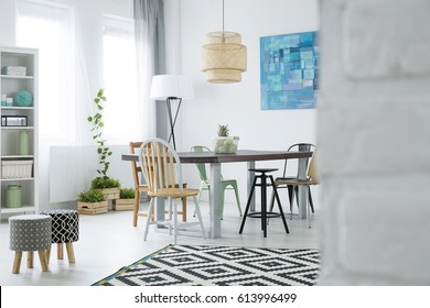 White dining room with window, lamp, stools and bookcase