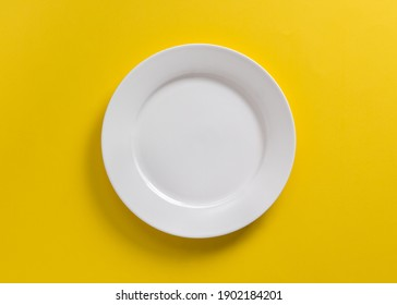White dinner plate on vibrant yellow