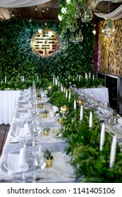 White dinner table decorated with greenery and white candles stands in the hall prepared for wedding