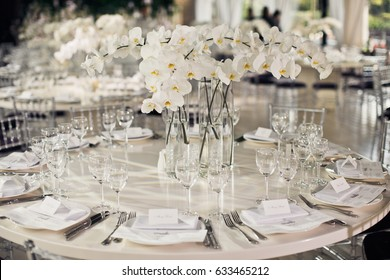White dinner table decorated with orchids