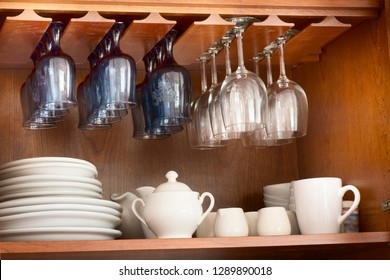 White dinnerware and blue and clear wine glasses neatly organized inside a wooden cupboard