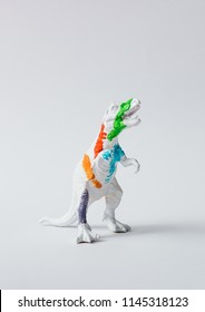 White dinosaur painted with vivid colors. Minimal surreal fun school concept.