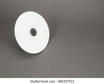 White disc moving, printable side up, isolated on gray background