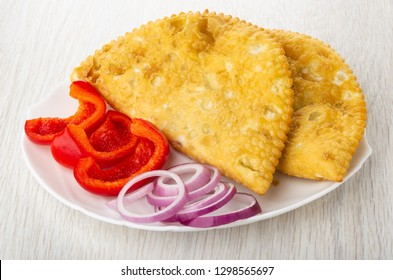 White dish with cheburek, pieces of red pepper, ring of onion on wooden table
