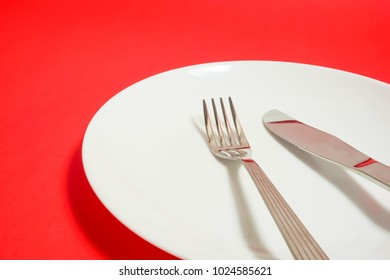 a white dish and a fork and a knife