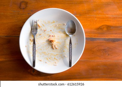 White dish with fork and spoon empty after eat.