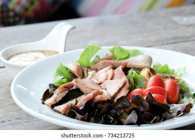 White dish of fresh vegetable salad with slices of grilled pork