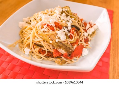 A white dish on a red place mat of with a mediterranean meal of spaghetti, feta cheese, aubergine (egg plant) and tomato