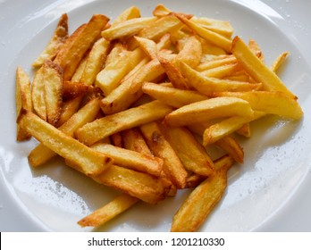 WHITE DISH PENTY OF GOLDEN CHIPS OR FRENCH FRIES READY TO BE EATEN WITH SALT