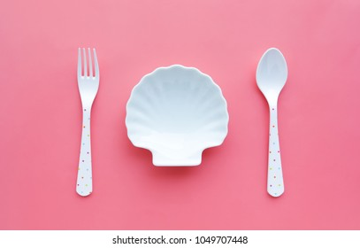 White of dish shellfish and spoon,fork on color background