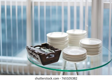 white dishs and spoon in wooden basket on glass table