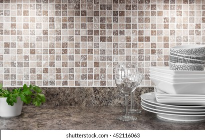 White dishware, wineglasses and green herbs on kitchen countertop.