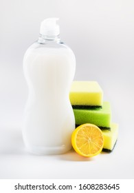 White dishwashing liquid in a plastic bottle, three foam sponges and lemon. Purity and household chemicals. Kitchen detergent on a white background. Front view.