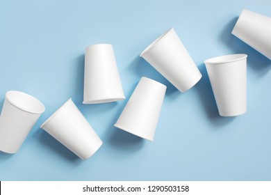 White disposable cups on the light blue background, top view