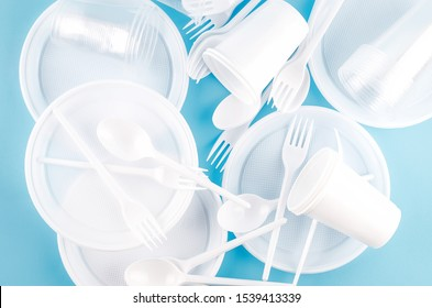 White Disposable cups, plates, forks, knives on light blue background close-up - Environmental problem concept