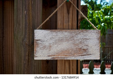 A white distressed blank sign board hanging from jute rope outdoors on old wooden fence.