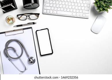 White doctors desk with stethoscope, blank screen smart phone, pen, keyboard and cup of coffee.Top view with copy space