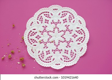 White doily and small crumbs on pink background