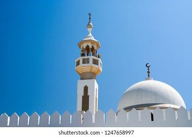 white dome and Minarette against blue sky in Oman