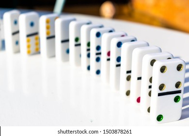 White domino tiles standing neatly on a white table ready to be pushed or fall over. Concept for family fun and dominoes games, organisation, OTC, neatness, pushed over the edge. Shadows from sunshine
