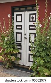 White door with hollyhocks. Shot from Faaborg, Denmark